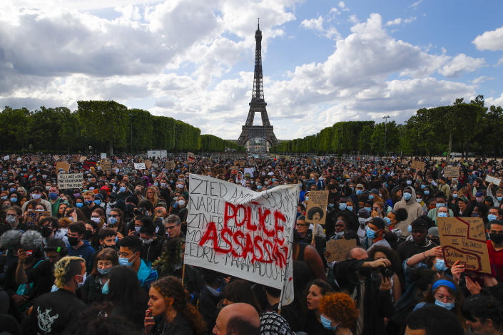 """FILE - In this June 6, 2020 file photo, hundreds of demonstrators gather near the Eiffel Tower, some with a banner reading """"Police, murderers"""" during a demonstration in Paris, France, to protest against the recent killing of George Floyd, a Black man who died in police custody in Minneapolis, U.S.A. As videos helped reveal many cases of police brutality, French civil rights activists voiced fears that a new security law would threaten efforts by people from minorities and poor neighborhoods to document incidents involving law enforcement officers. French President Emmanuel Macron's government is pushing a new security bill that would notably make it illegal to publish images of officers with intent to cause them harm. (AP Photo/Francois Mori, File)"""