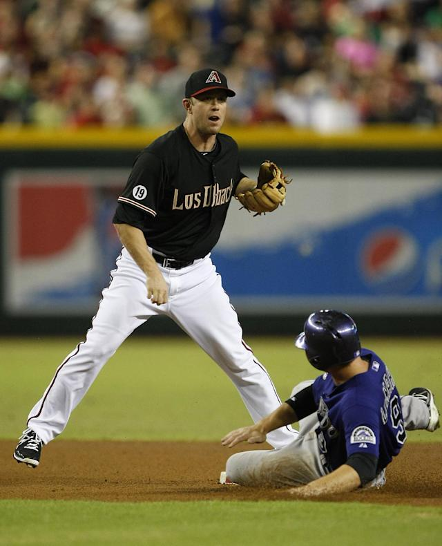 Arizona Diamondbacks second baseman Aaron Hill, left, turns the double play while avoiding Colorado Rockies' DJ LeMahieu (9) in the first inning during a baseball game on Saturday, Sept. 14, 2013, in Phoenix. (AP Photo/Rick Scuteri)