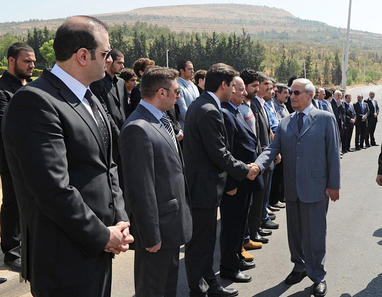 In this photo released by the Syrian official news agency SANA, Farouk Sharaa, Bashar Assad's vice president, right, gives his condolences to the relatives of Assad's inner circle, who were killed on Wednesday by a bomb, as he attends their funeral processions, in Damascus, Syria, Friday, July, 20, 2012. A bombing in Damascus claimed by Syrian rebels Wednesday killed key figures in President Bashar Assad's inner circle. (AP Photo/SANA)
