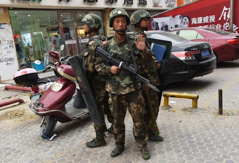 Paramilitary police stand guard outside a shopping mall in Hotan, in China's western Xinjiang region, which has seen an uptick in violence in recent years (AFP Photo/GREG BAKER)
