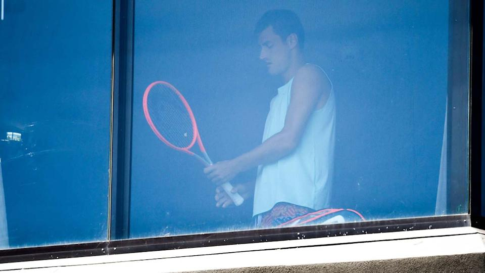 Bernard Tomic, pictured here exercising in his hotel room in Melbourne.
