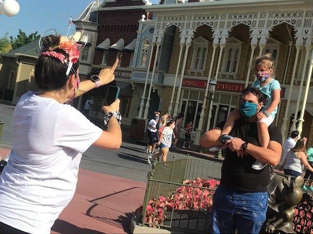 A family all wearing masks, stops for photos at Magic Kingdom.