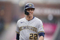 Milwaukee Brewers' Christian Yelich jokes with first base coach Quintin Berry after Yelich drew a walk from Colorado Rockies starting pitcher German Marquez during the first inning of a baseball game Thursday, June 17, 2021, in Denver. (AP Photo/David Zalubowski)