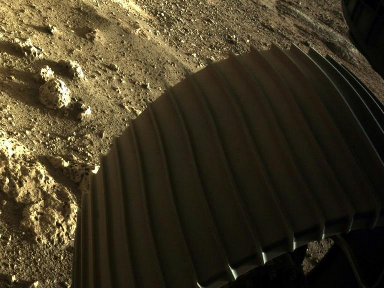 A second color image shows one of the rover's six wheels, with several honeycombed rocks thought to be more than 3.6 billion years old lying next to it