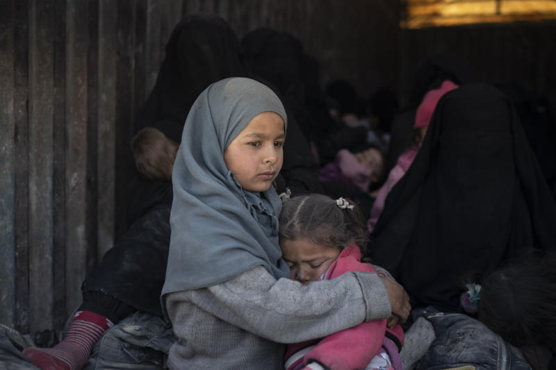 Children ride in the back of a truck that is part of a convoy evacuating hundreds out of the last territory held by Islamic State militants, in Baghouz, eastern Syria, Wednesday, Feb. 20, 2019. The evacuation signals the end of a week long standoff and opens the way to U.S.-backed Syrian Democratic Forces (SDF) recapture the territory. (AP Photo/Felipe Dana)