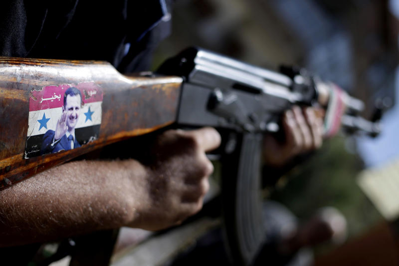 """FILE - In this Wednesday, Aug. 21, 2013 file photo, a Syrian military soldier holds his AK-47 with a sticker of Syrian President Bashar Assad and Arabic that reads, """"Syria is fine,"""" as he stands guard at a check point on Baghdad street, in Damascus, Syria. The signs would all seem bad for President Bashar Assad. Blasts echo all day long over the Syrian capital as troops battle rebels entrenched on its eastern doorstep. The government admits the economy is devastated. And now allegations of a horrific chemical attack have given new life to calls for international action against his regime. (AP Photo/Hassan Ammar, File)"""
