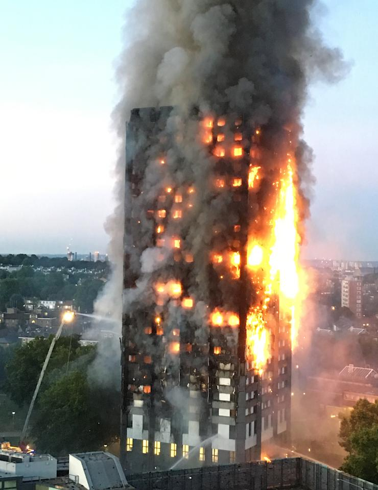 <p>In one of the most distressing photos of the year, thick smoke rises into the cloudless sky as over 200 firefighters from across London continue tackle the blaze at Grenfell Tower in North Kensington. Fire crews were called to the high-rise residential block on the Lancaster West housing estate in White City just before 1am on 14 June. The devastating fire killed 71 people. (REX/Shutterstock) </p>