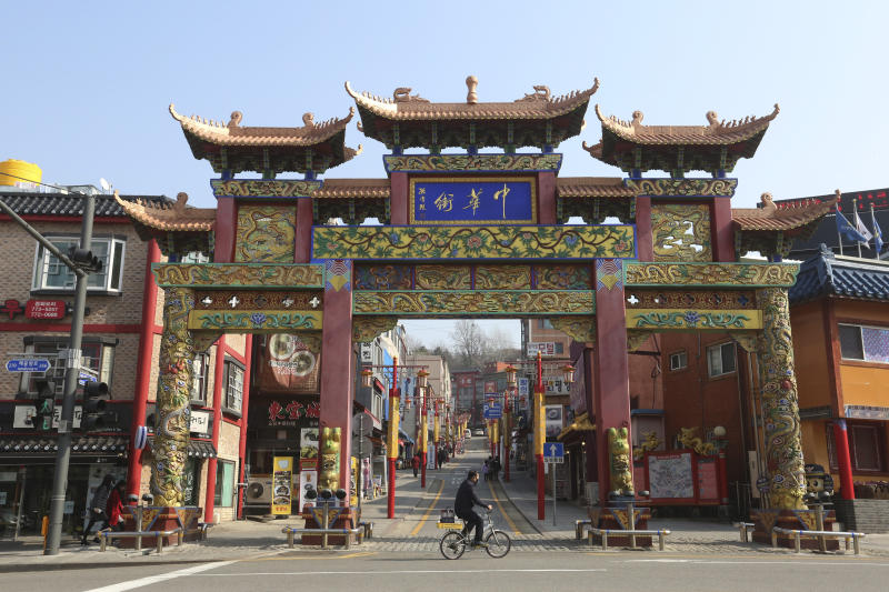 In this Feb. 14, 2020. photo, a man wearing a face mask rides a bicycle to pass the Chinatown's main entrance gate in Incheon, South Korea. Even as cases and deaths from the new virus mount, fear is advancing like a tsunami - and not just in the areas surrounding the Chinese city of Wuhan, the center of the outbreak that has been declared a global health emergency. A restaurant owner in the Chinatown says visitors have dropped by 90%. (AP Photo/Ahn Young-joon)