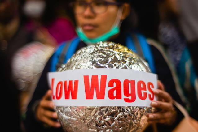 "<p>An activist from the Asian Migrants Coordinating Body holds a sign that reads ""Low Wages"" during a protest urging the Immigration Department to review its accommodation and visa polices for foreign domestic helpers on International Women's Day in Hong Kong on March 8, 2018. (Photo: Anthony Wallace/AFP/Getty Images) </p>"