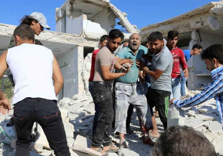 Syrian civilians help a wounded man following reported air strikes by regime forces  on Maaret al-Numan in Syria's northwestern Idlib province on July 23, 2019