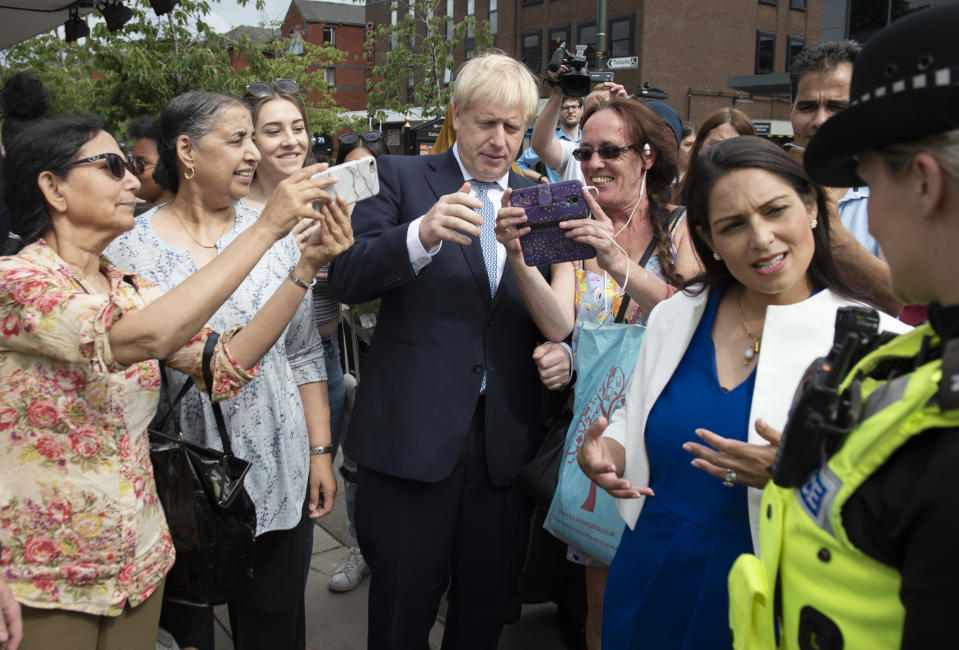 "Britain's Prime Minister Boris Johnson (C) poses for selfie photographs with members of the public as he takes a walkabout with Britain's Home Secretary Priti Patel (2R) and members of West Midlands Police in Birmingham, central England on July 26, 2019. - Johnson pledged to start recruiting 20,000 new police officers as one of a number of anouncements on his government's domestic policy agenda during his debut statement in the House of Commons as Prime Minister on July 25. Meanwhile, Johnson has deliberately set Britain on a ""collision course"" with the EU over Brexit negotiations, Ireland's foreign minister was quoted as saying on Friday. (Photo by Geoff Pugh / POOL / AFP) (Photo credit should read GEOFF PUGH/AFP via Getty Images)"