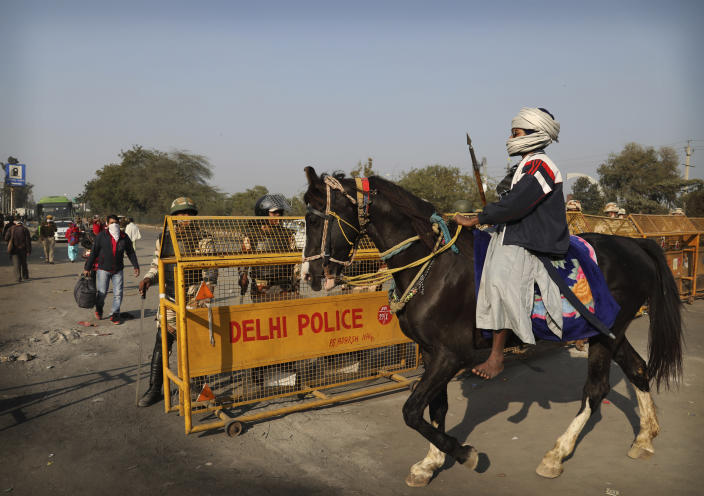 A Nihang or a Sikh warrior on a horse arrives at Singhu, Delhi-Haryana border for ongoing farmers protest against three farm bills, in New Delhi, India, Wednesday, Jan. 27, 2021. Tens of thousands of farmers who stormed the historic Red Fort on India's Republic Day are again camped outside the capital after the most volatile day of their two-month standoff left one protester dead and more than 300 police officers injured. (AP Photo/Manish Swarup)