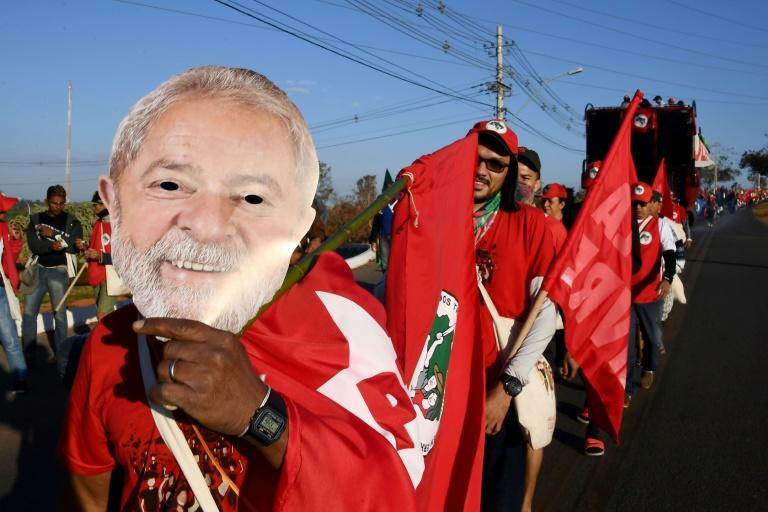 "Members of the Landless Movement holding masks of former Brazilian President Luiz Inacio Lula da Silva take part in the ""Free Lula"" march near Brasilia"