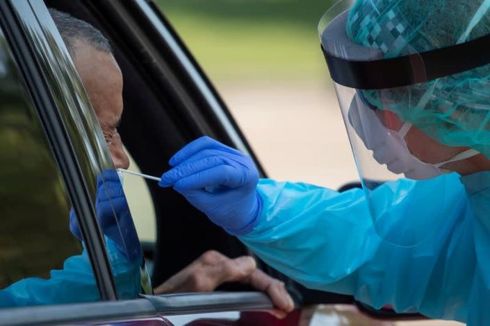 FILE PHOTO: Health care worker uses a swab to test man at COVID-19 drive in testing location in Houston, Texas