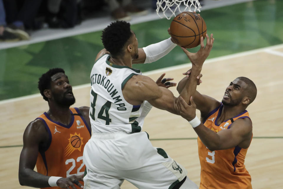 Milwaukee Bucks forward Giannis Antetokounmpo (34) drives to the basket between Phoenix Suns center Deandre Ayton (22) and guard Chris Paul (3) during the second half of Game 4 of basketball's NBA Finals Wednesday, July 14, 2021, in Milwaukee. (AP Photo/Aaron Gash)