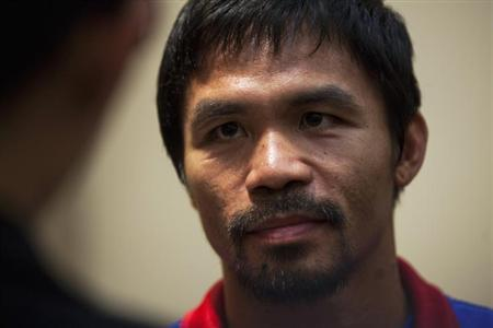 Boxer Manny Pacquiao of the Philippines looks on during a news conference at the Venetian Macao hotel in Macau November 19, 2013. REUTERS/Tyrone Siu