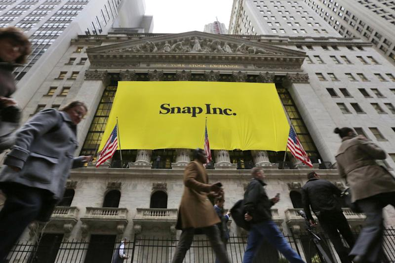 """People pass by the New York Stock Exchange after the banner for the Snap Inc. IPO was raised on the building's facade, Wednesday, March 1, 2017. Snap Inc. is expected to start trading on the New York Stock Exchange on Thursday under the symbol """"SNAP."""" (AP Photo/Richard Drew)"""