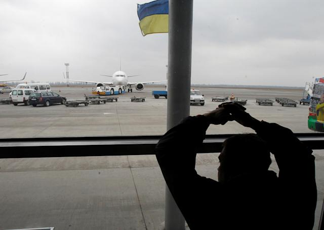 FILE PHOTO: A passenger looks through the window at Borispol airport near Kiev, March 21, 2012. Borispol will be Ukraine's main air hub during the Euro 2012 football championship. REUTERS/Gleb Garanich/File Photo