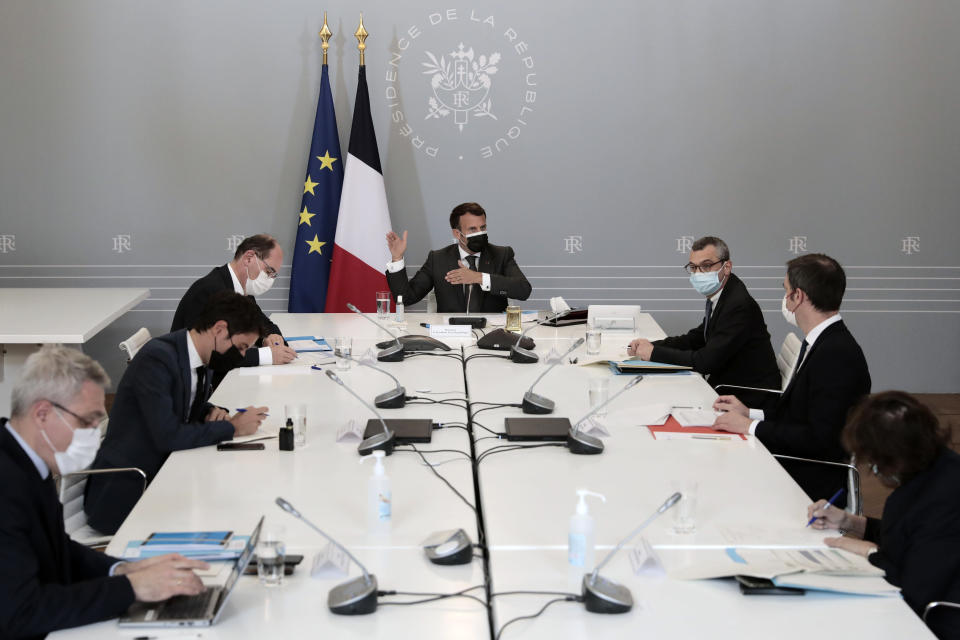 French President Emmanuel Macron, center attends a weekly meeting about the vaccination campaign, with Prime Minister Jean Castex, left, Secretary General of the Elysee Palace Alexis Kohler, right, Government's spokesman Gabriel Attal, second left, Health Minister Olivier Veran, second right, at the Elysee presidential palace in Paris, France, Tuesday April, 20, 2021. (AP Photo/Lewis Joly, pool)