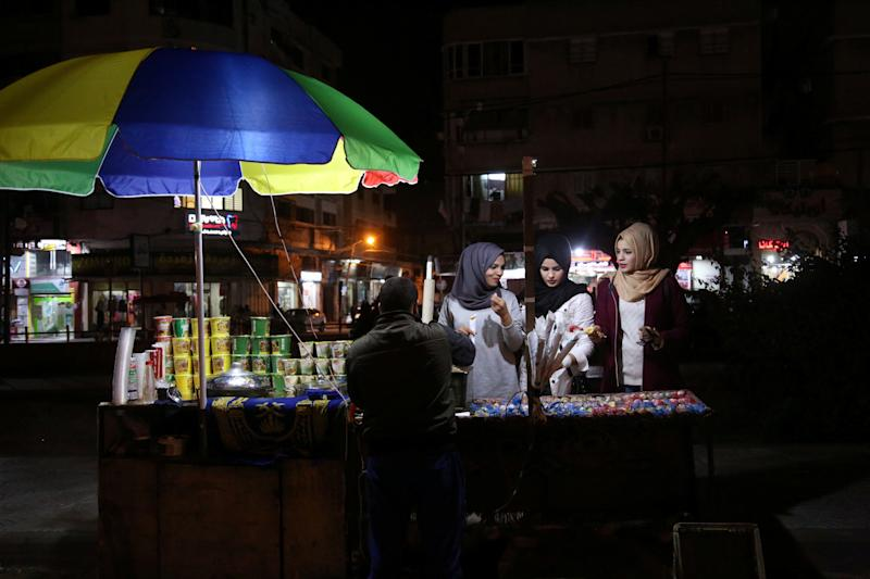(L-R) Palestinian Saly Abu Amra, 23, Hana Abu El-Roos, 18, and Wessal Abu Amra, 17, buy snacks from a vendor in Gaza City, Nov. 24, 2018. (Photo: Samar Abo Elouf/Reuters)
