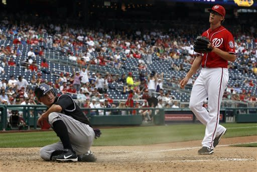 Colorado Rockies' Jordan Pacheco, left, scores the winning run on a wild pitch from Washington Nationals relief pitcher Tyler Clippard, right, during the ninth inning of a baseball game on Sunday, July 8, 2012, in Washington. The Rockies won 4-3. (AP Photo/Alex Brandon)