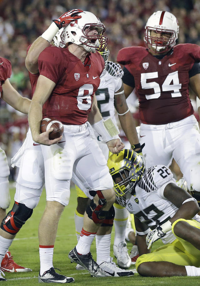 Stanford quarterback Kevin Hogan (8) celebrates with tight end Charlie Hopkins (obscured) and guard David Yankey (54) after running for an 11-yard touchdown against Oregon during the second quarter of an NCAA college football game in Stanford, Calif., Thursday, Nov. 7, 2013. Oregon linebacker Derrick Malone (22) sits on the ground. (AP Photo/Marcio Jose Sanchez)