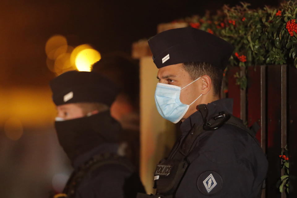 """French police officers stand outside a high school after a history teacher who opened a discussion with students on caricatures of Islam's Prophet Muhammad was beheaded, Friday, Oct. 16, 2020 in Conflans-Sainte-Honorine, north of Paris. Police have shot the suspected killer dead. The teacher had received threats after opening a discussion """"for a debate"""" about the caricatures about 10 days ago, the police official told The Associated Press. (AP Photo/Michel Euler)"""