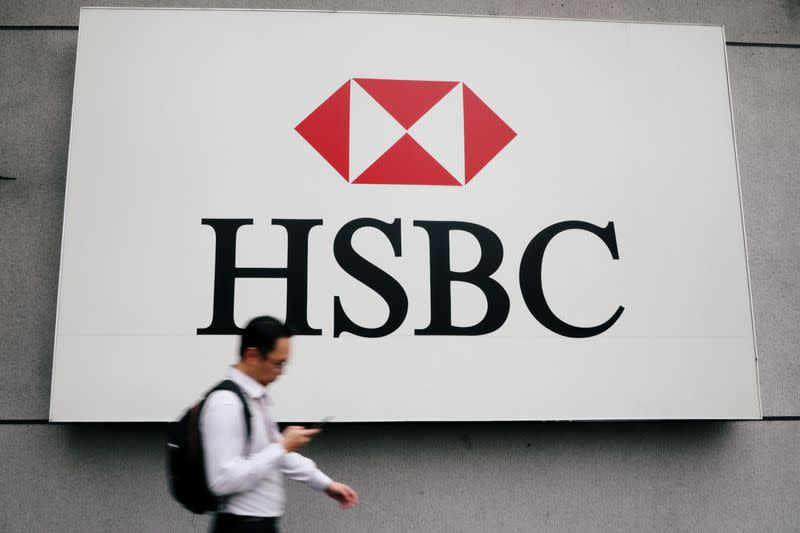 FILE PHOTO: A man walks past a logo of HSBC at its headquarters in Kuala Lumpur