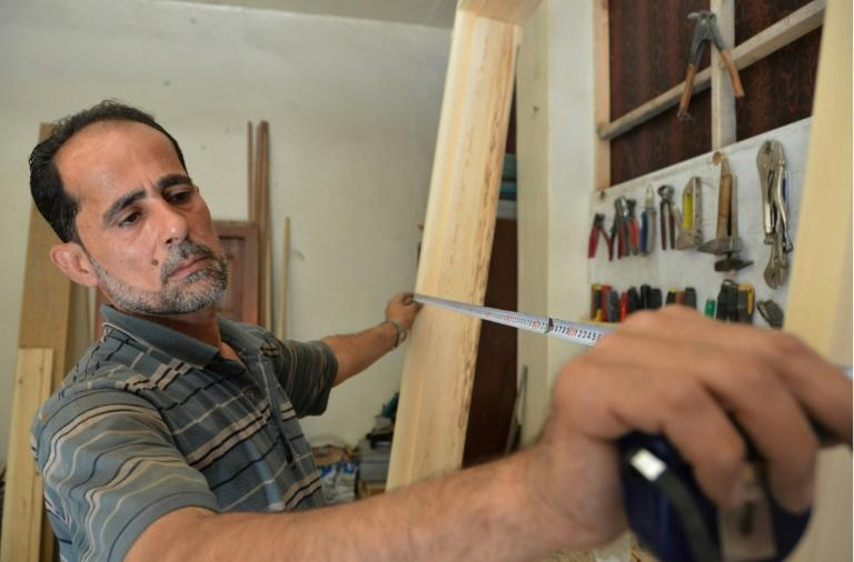 Syrian furniture maker Hussam Obayd measures wood at his workshop in the town of Saqba