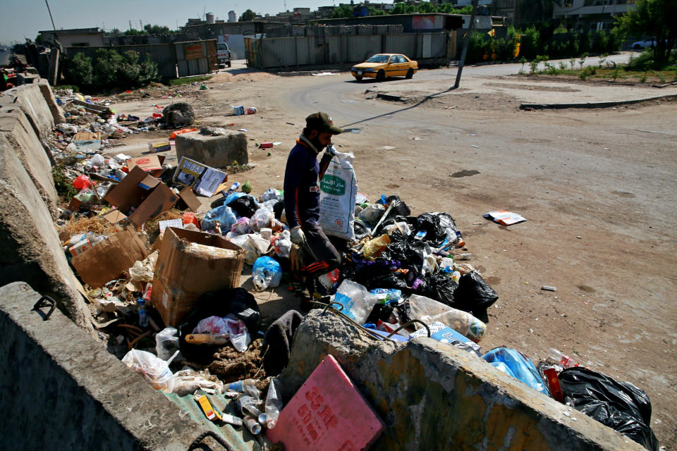 A man searches for recycled items in a landfill in Baghdad, Iraq, Tuesday, Oct. 20, 2020. Iraq is in the throes of an unprecedented liquidity crisis, as the cash-strapped state wrestles to pay public sector salaries and import essential goods while oil prices remain dangerously low. (AP Photo/Khalid Mohammed)
