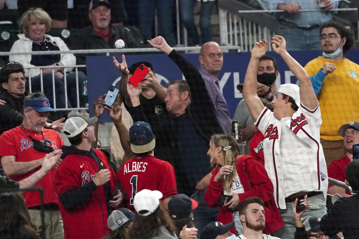 Fans reach for a foul ball during a baseball game between the Philadelphia Phillies and the Atlanta Braves, Friday, May 7, 2021, in Atlanta. Truist Park was open to 100% capacity. (AP Photo/John Bazemore)