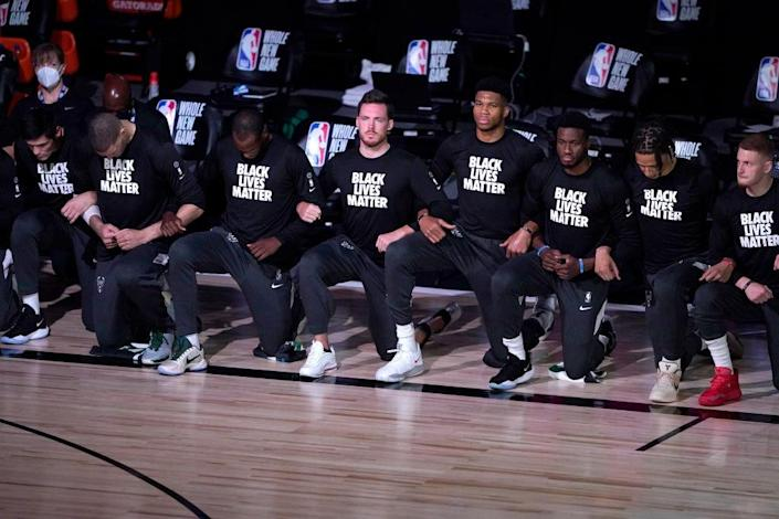 Players kneel and wear Black Lives Matter shirts before the start of an NBA basketball game between the Milwaukee Bucks and the Boston Celtics Friday, July 31, 2020, in Lake Buena Vista, Florida. (Photo by Ashley Landis-Pool/Getty Images)