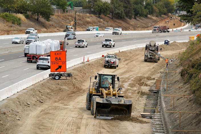 Traffic flows past construction work on eastbound Highway 50 in Sacramento, Calif., on Aug. 12, 2021. The work is part the California Department of Transportations comprehensive project that would improve Highway 50 with the construction of High Occupancy Vehicle lanes.