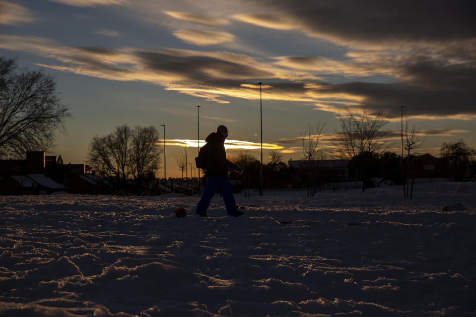 A man walks through the snow as the sunset in Rivas Vaciamadrid, Spain, Sunday, Jan. 10, 2021. A large part of central Spain including the capital of Madrid are slowly clearing snow after the country's worst snowstorm in recent memory. (AP Photo/Manu Fernandez)