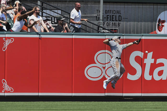Miami Marlins left fielder Derek Dietrich just misses a long fly ball hit by Baltimore Orioles' Mark Trumbo in the third inning of baseball game, Sunday, June 17, 2018, in Baltimore. Trumbo earned a double on the play. (AP Photo/Gail Burton)