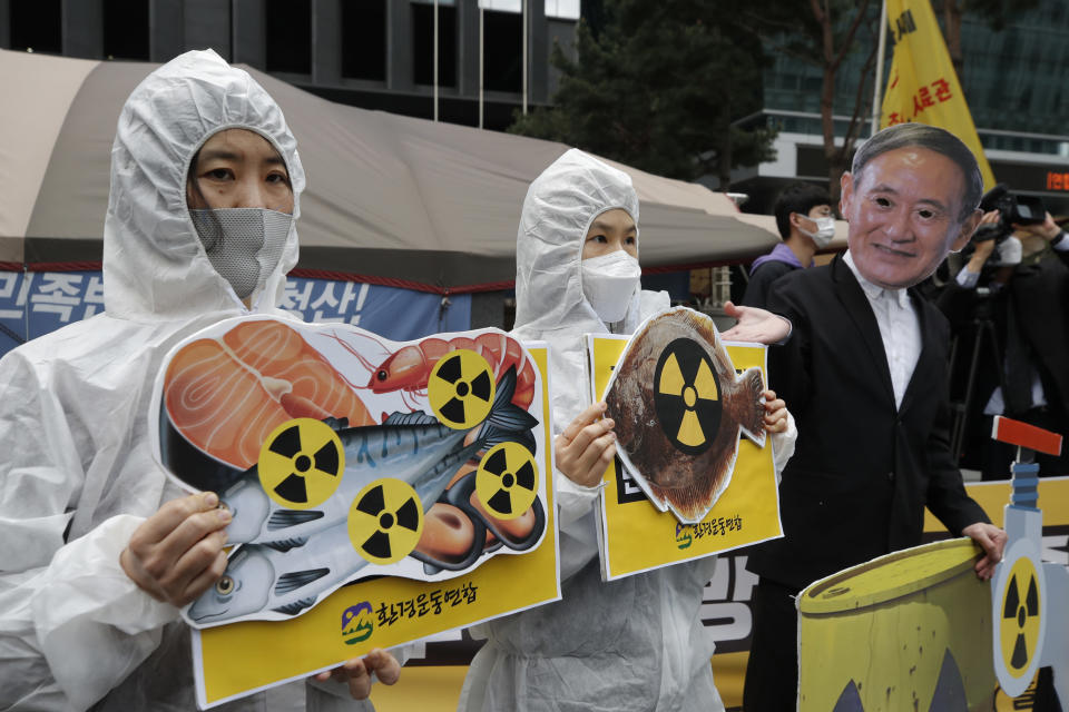 Environmental activists wearing a mask of Japanese Prime Minister Yoshihide Suga and protective suits perform to denounce the Japanese government's decision on Fukushima water, near the Japanese embassy in Seoul, South Korea, Tuesday, April 13, 2021. Japan's government decided Tuesday to start releasing massive amounts of treated radioactive water from the wrecked Fukushima nuclear plant into the Pacific Ocean in two years — an option fiercely opposed by local fishermen and residents. (AP Photo/Lee Jin-man)