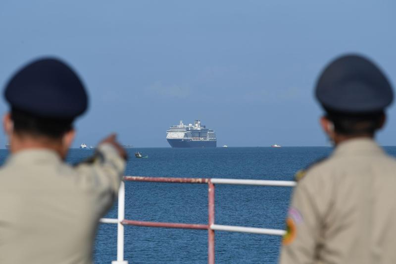 TOPSHOT - The Westerdam cruise ship is seen past Cambodian policemen as it approaches port in Sihanoukville, Cambodia's southern coast on February 13, 2020, where the liner had received permission to dock after been refused entry at other Asian ports due to fears of the COVID-19 coronavirus. - Japan, Guam, the Philippines, Taiwan and Thailand all refused to allow the ship to dock, despite operator Holland America insisting there were no cases of the deadly disease -- which has killed over 1,100 -- on board. (Photo by TANG CHHIN Sothy / AFP) (Photo by TANG CHHIN SOTHY/AFP via Getty Images): Getty Images