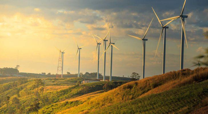 A shot of wind energy mills with green hills and the skyline in the background.