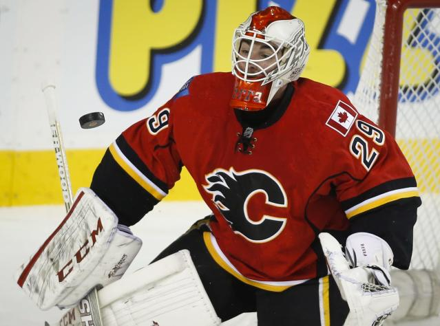 Calgary Flames goalie Reto Berra, from Switzerland, makes a save against the San Jose Sharks during the first period of an NHL hockey game Tuesday, Nov. 12, 2013, in Calgary, Alberta. (AP Photo/The Canadian Press, Jeff McIntosh)