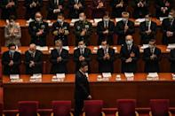Delegates applaud as China's President Xi Jinping arrives for the opening session of the National People's Congress at the Great Hall of the People in Beijing