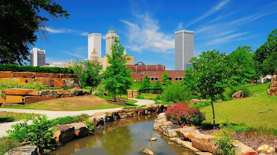 """""""Tulsa downtown skyline from a park with trees, grass, rocks, and a stream in the foreground."""