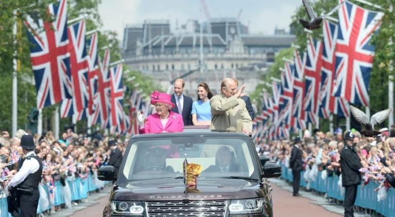 Britain's Queen Elizabeth II (L) and Prince Philip (R), Duke of Edinburgh wave to guests as they are followed in a convoy by Prince William, Catherine, Duchess of Cambridge and Prince Harry on June 12, 2016