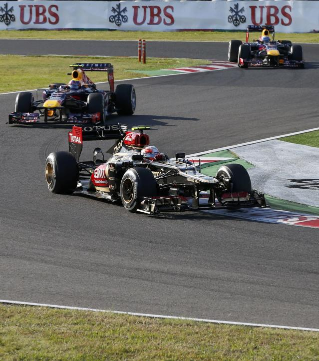Lotus Formula One driver Romain Grosjean (R) of France drives ahead of Red Bull Formula One driver Mark Webber of Australia during the Japanese F1 Grand Prix at the Suzuka circuit October 13, 2013. REUTERS/Toru Hanai (JAPAN - Tags: SPORT MOTORSPORT F1)