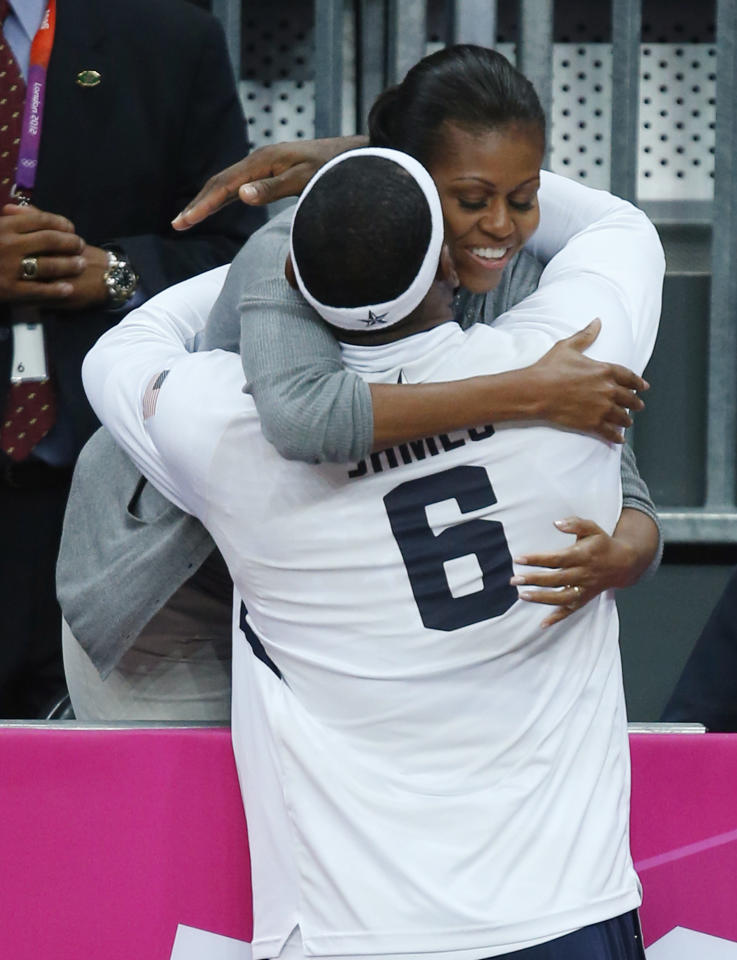 First Lady Michelle Obama hugs USA's Lebron James after USA defeated France in a preliminary men's basketball game at the 2012 Summer Olympics, Sunday, July 29, 2012, in London. (AP Photo/Jae C. Hong)