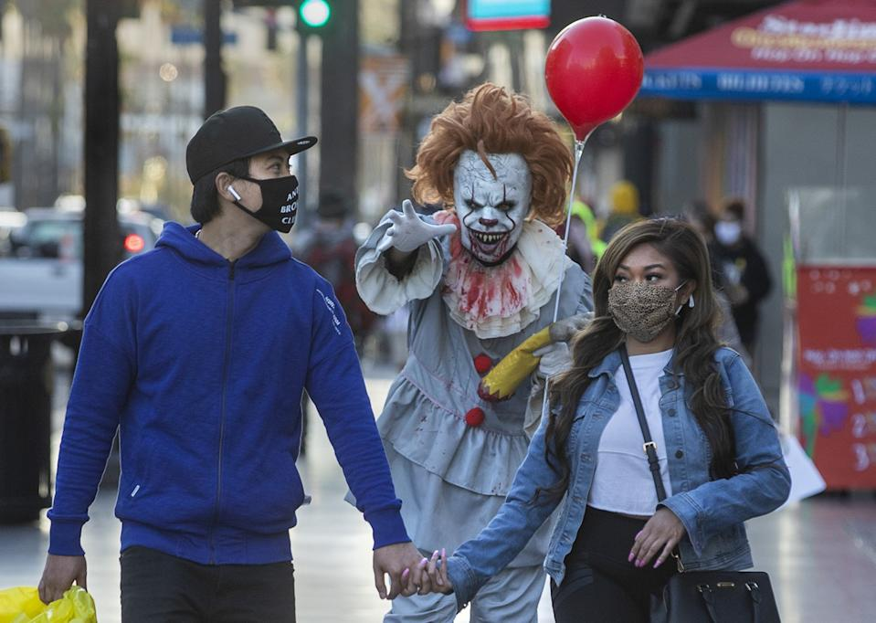 A street performer dressed as Pennywise the clown holds an arm out toward a masked couple walking on the sidewalk