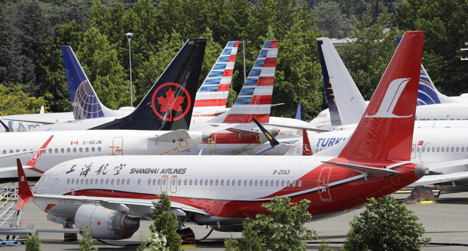 """Dozens of grounded Boeing 737 MAX airplanes crowd a parking area adjacent to Boeing Field Thursday, June 27, 2019, in Seattle. A new software problem has been found in the troubled Boeing 737 Max that could push the plane's nose down automatically, and fixing the flaw is almost certain to further delay the plane's return to flying after two deadly crashes. Boeing said Wednesday, June 26, 2019, that the FAA """"identified an additional requirement"""" for software changes that the aircraft manufacturer has been working on for eight months, since shortly after the first crash. (AP Photo/Elaine Thompson)"""
