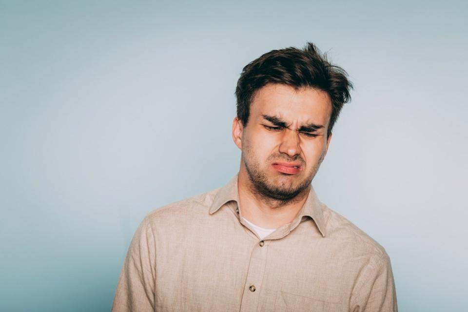 nausea aversion repulsion. reluctant man grimacing in disgust. portrait of a young brunet guy on light background. emotion facial expression. feelings and people reaction concept.