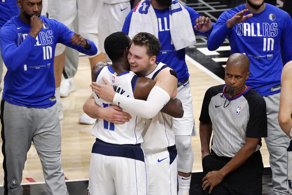 Dallas Mavericks guard Luka Doncic, center right, hugs forward Tim Hardaway Jr. after the Mavericks defeated the Los Angeles Clippers 105-100 in Game 5 of an NBA basketball first-round playoff series Wednesday, June 2, 2021, in Los Angeles. (AP Photo/Mark J. Terrill)