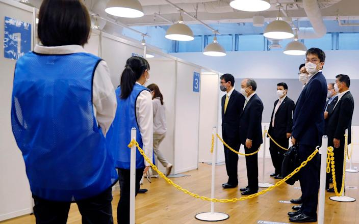 Covid 19 Vaccine Minister Taro Kono, center left, and Masayoshi Son, chief executive of technology company SoftBank Group Corp., center right, visit an inoculation site set up by Japanese technology company SoftBank Group Corp. at a WeWork office Tuesday, June 15, 2021, in Tokyo. - AP