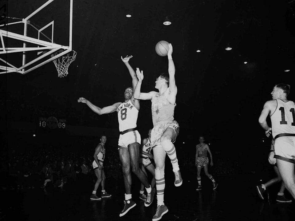 """George Mikan, right, six-foot, ten-inch center for the Minneapolis Lakers, goes way up to make a goal as New York Knickerbockers' six-foot, seven-inch center Nat """"Sweetwater"""" Clifton  (8) makes an unsuccessful attempt to defend on April 8, 1953 at the 69th Regiment Armory in New York.  (AP Photo)"""